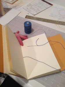 Hand-sewing the books with linen thread.