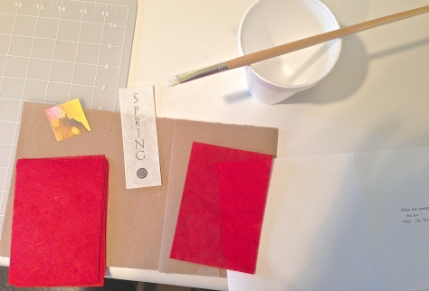 Gluing the decorative papers that illuminate the seasonal title pages.