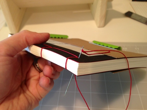 Sewing the book with red linen thread.