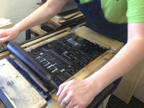 Rolling the ink carefully over the type forme.