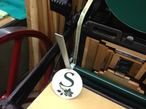 "An ""S"" on the Press.  Coasters are letterpress printed on our 1914 Chandler & Price foot-treadled press."